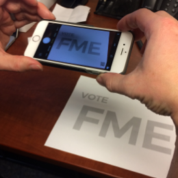Scanning the QR code on a Vote FME poster
